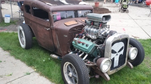 The rust surface finish, few mufflers on the exhaust headers and Punisher spray painted in the grill are clues that this car is all about fun and is a rat rod