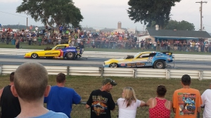 2 Funny cars drag racing. Funny cars are purpose built drag cars that go very fast.